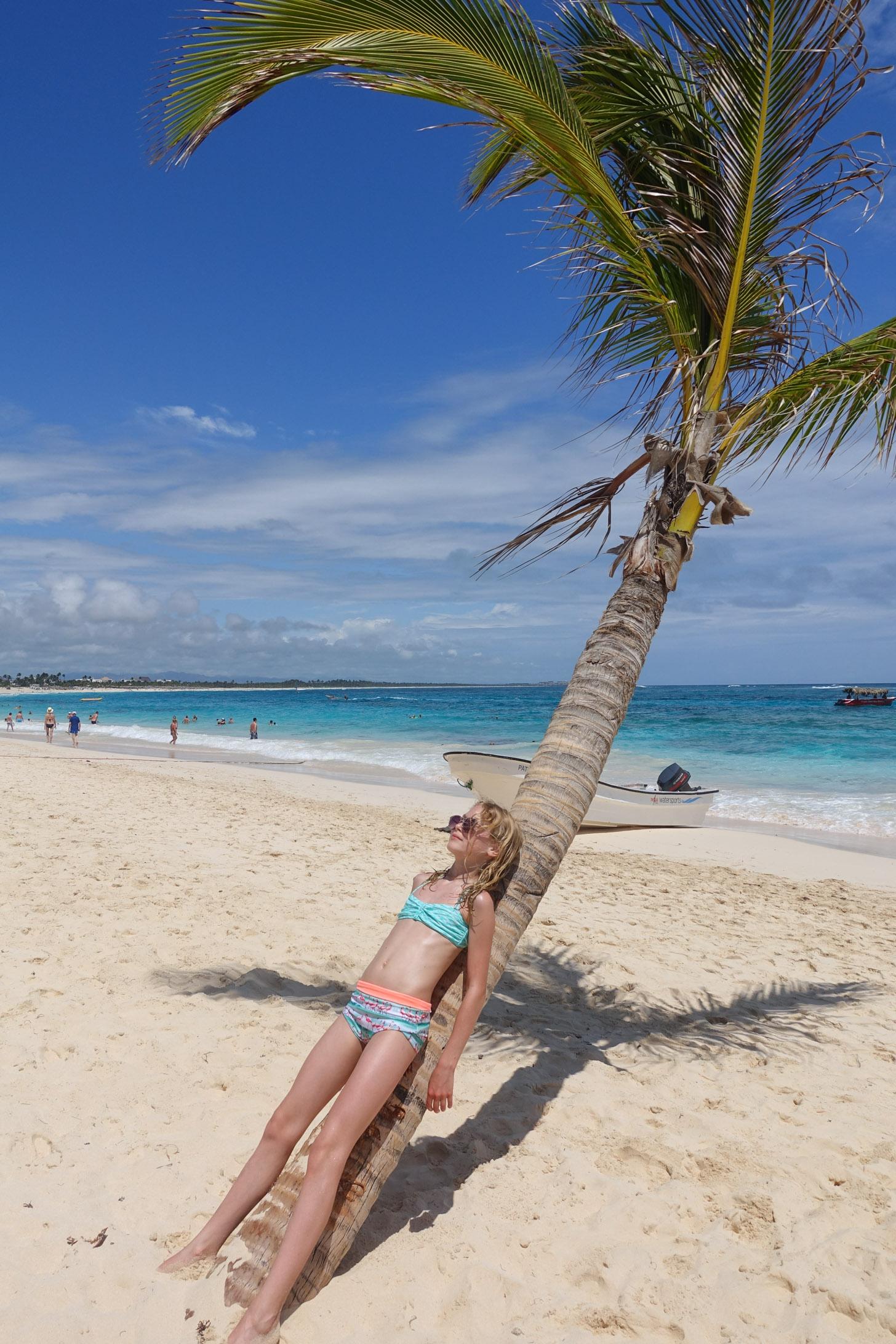 Een kind die heerlijk tegen een palmboom van de zon geniet